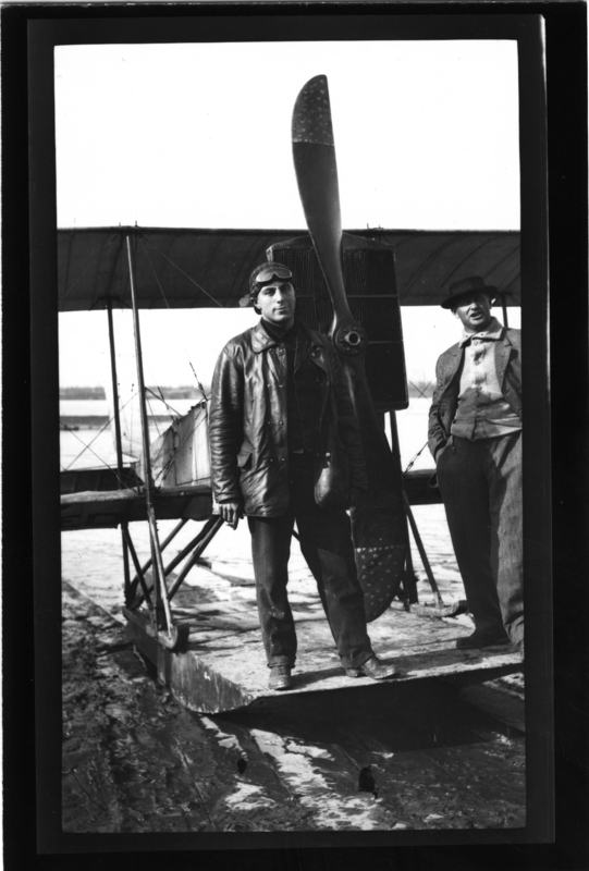 """First plane down Mississippi River. Janas, pilot, killed in Russia in 1917, stands in front of biwing airplane. Harris Hurlbert in sport jacket also in picture."" Friars Point, Miss. Painter Collection. Call Number: PI/1988.0006 (MDAH)"