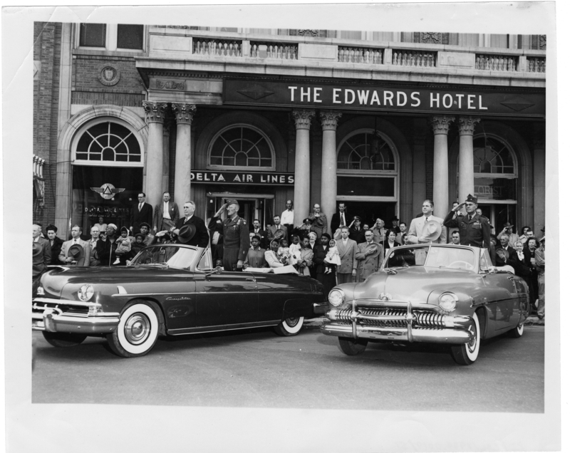 Gov. White, Mayor Thompson and military officers salute from convertible automobiles parked in front of The Edwards Hotel. Call Number: PI/COL/1984.0019, item 51 (MDAH)